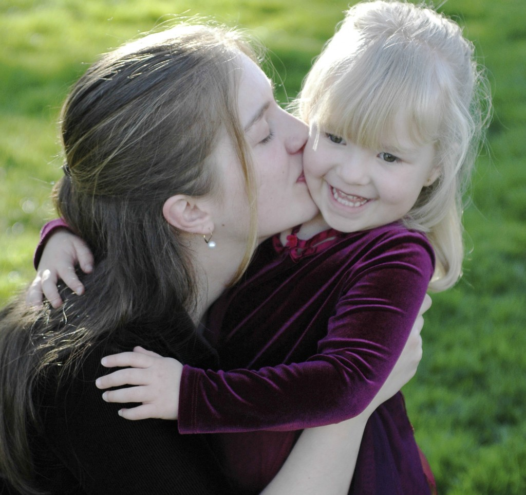 Image of a young woman kissing her daughter